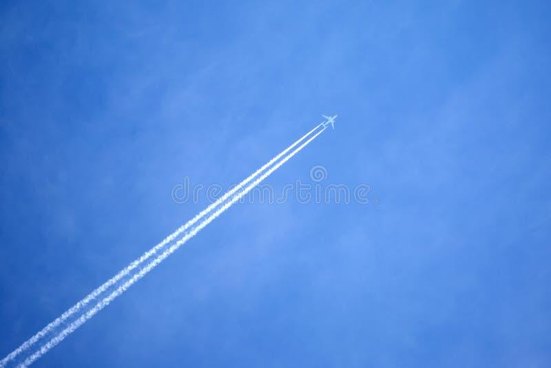 Pasażera samolotu odrzutowego latanie w jasnym niebieskim niebie, opuszcza białego ślad obraz stock