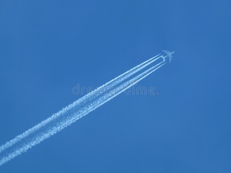 Pasażera samolotu odrzutowego latanie w jasnym niebieskim niebie, opuszcza białego ślad fotografia stock