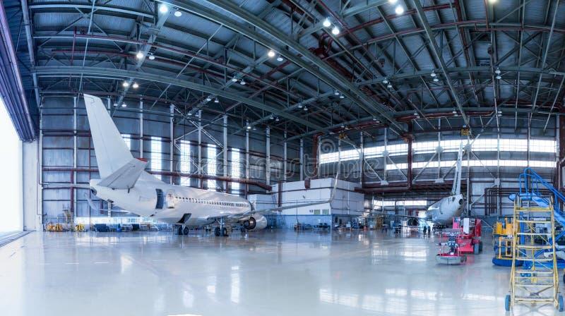 Pasażerscy samoloty pod utrzymaniem Sprawdzać machinalnych systemy dla lot operacji Panorama samoloty w hangarze zdjęcie royalty free
