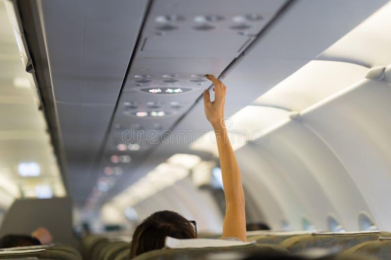 Pasażerska ręka przystosowywa powietrze uwarunkowywać nad siedzenie podczas gdy na pokładzie samolotu obrazy royalty free