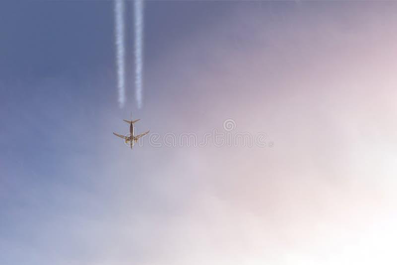Pasażerska samolotowa latająca wysokość w jasnym niebie opuszcza biel wlec Duży płaski latanie podczas zmierzchu czasu z dramatyc fotografia royalty free