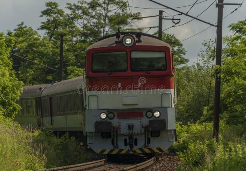 Pasażerski dieslowski czerwony duży pociąg blisko Kysak stacji w lato gorącym ranku fotografia royalty free