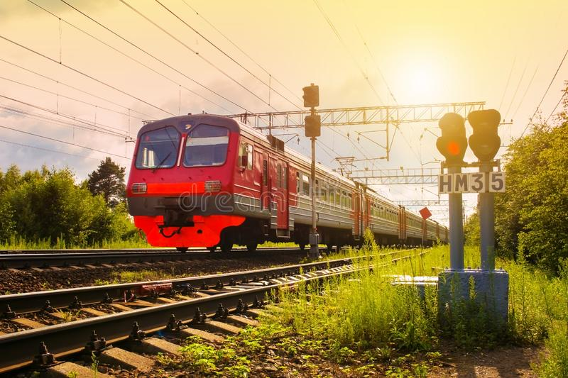Pasażerski elektryczny pociąg, ruszający się przeciw zmierzchowi i światła ruchu w przedpolu zdjęcie stock