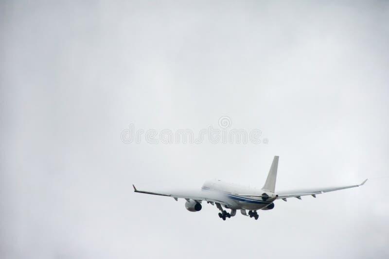 Pasażerski liniowiec bierze daleko w niebo od lotniskowego pasa startowego w chmurnej pogodzie z deszczem zdjęcie royalty free
