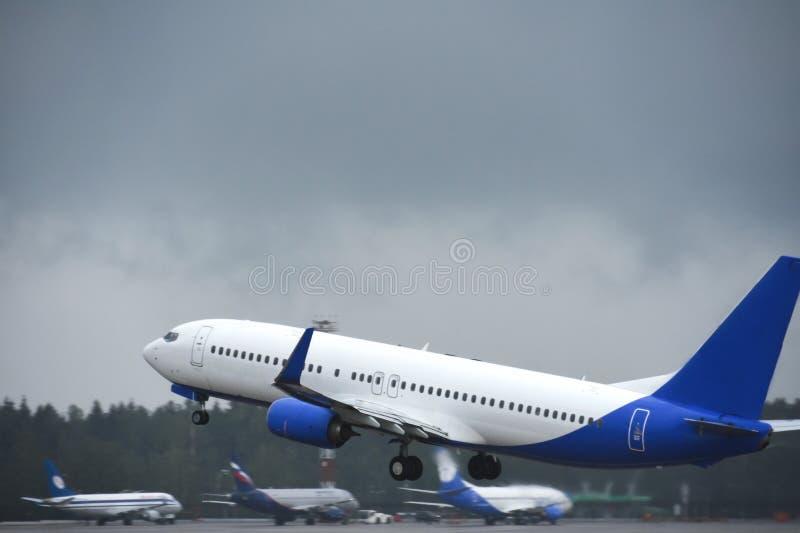 Pasażerski liniowiec bierze daleko w niebo od lotniskowego pasa startowego w chmurnej pogodzie z deszczem zdjęcia stock