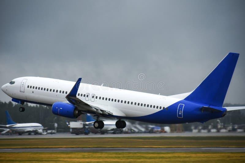 Pasażerski liniowiec bierze daleko w niebo od lotniskowego pasa startowego w chmurnej pogodzie z deszczem obrazy royalty free