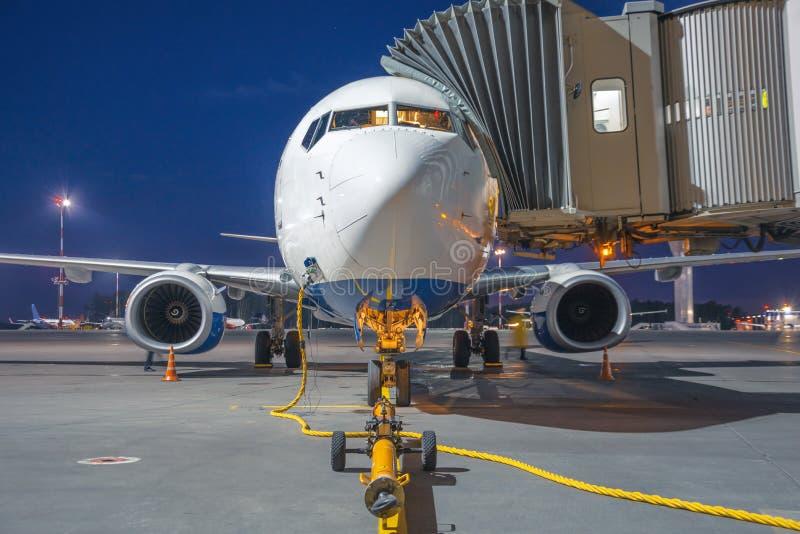 Pasażerski samolot jest parkujący związany drabiną przy śmiertelnie budynkiem w lotnisku, blisko frontowego przyczepy winch dla h fotografia royalty free