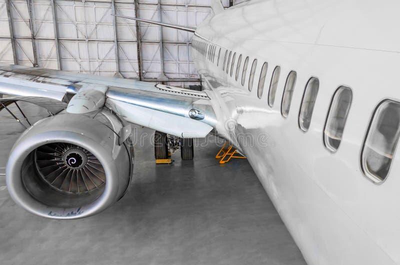Pasażerski samolot na utrzymaniu dżetowego silnika i samolotu hangar zdjęcia stock