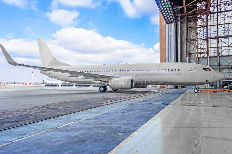 Pasażerski samolot na utrzymaniu silnika i kadłuba naprawa w lotniskowym hangarze obraz stock