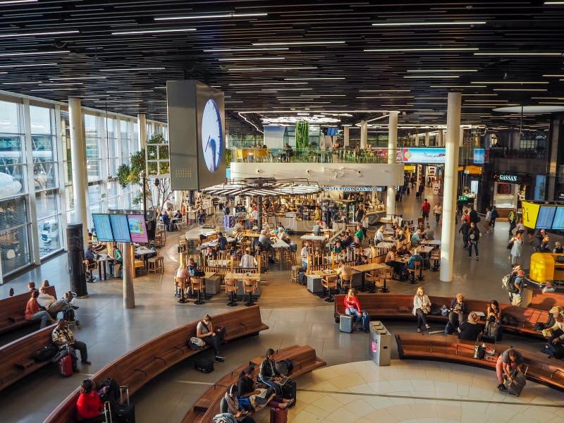Pasażery siedzi w holu terenie przy Schiphol lotniskiem międzynarodowym obrazy royalty free