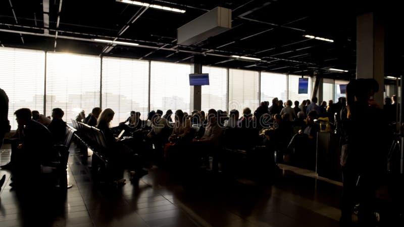 Pasażery siedzi wyjściowego hol i czeka wsiadać, lotniskowy terminal fotografia stock