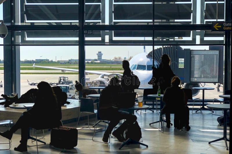 Pasażery zabija czas w lotniskowy śmiertelnie, czekający wsiadającym dalej samolot zdjęcie stock