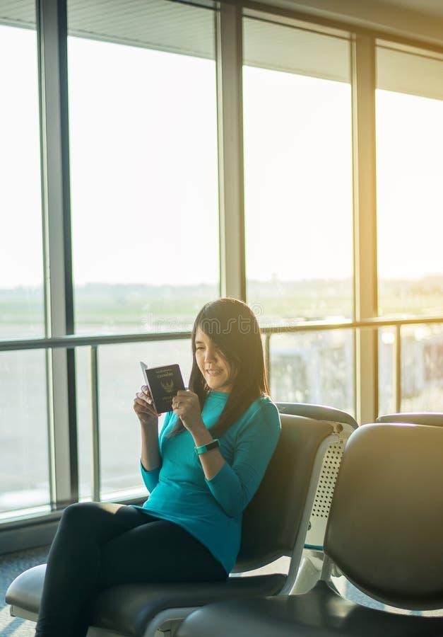 Pasajero asiático de la mujer que celebra el pasaporte y el vuelo de comprobación o planificador en línea del incorporar y del vi imagen de archivo