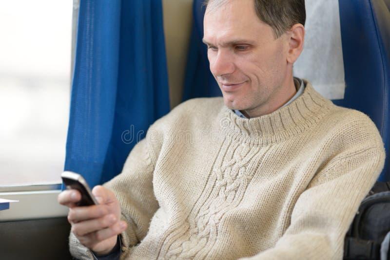 Pasajero con el teléfono celular en un tren imagen de archivo libre de regalías