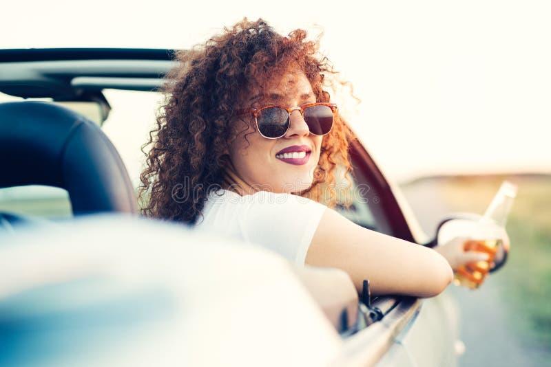 Pasajero de la mujer en viaje por carretera en coche convertible imagenes de archivo