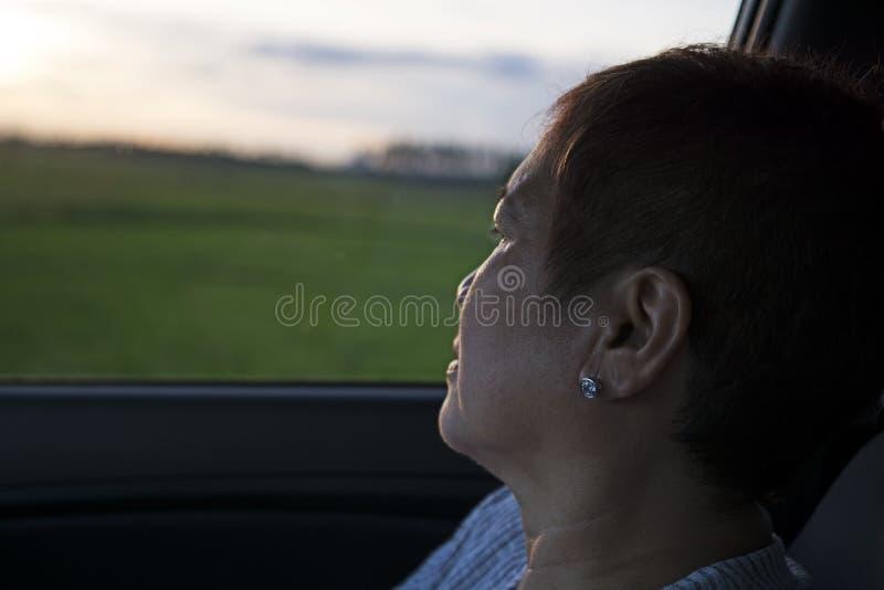 Pasajero de la mujer que mira hacia fuera en una ventanilla del coche fotografía de archivo
