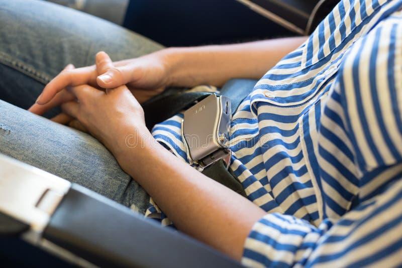Pasajero femenino con el cinturón de seguridad sujetado mientras que se sienta en el aeroplano para el vuelo seguro foto de archivo