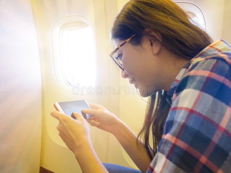 Pasajero femenino sonriente que se sienta cerca de asiento de ventana imagenes de archivo