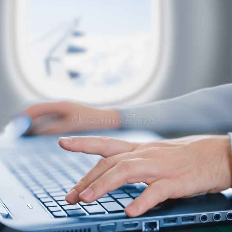 Pasajero que usa el ordenador portátil en aeroplano fotos de archivo