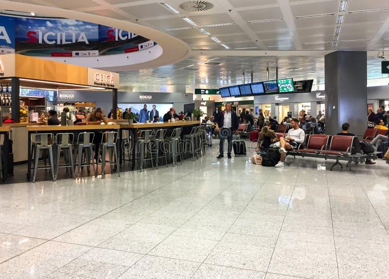 Pasajeros en la sala de espera antes de la salida en el terminal de aeropuerto de Milán-Malpensa 1 imágenes de archivo libres de regalías