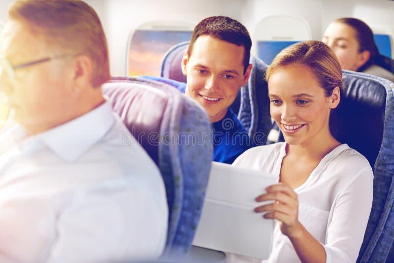 Pasajeros felices con café que hablan en el avión foto de archivo