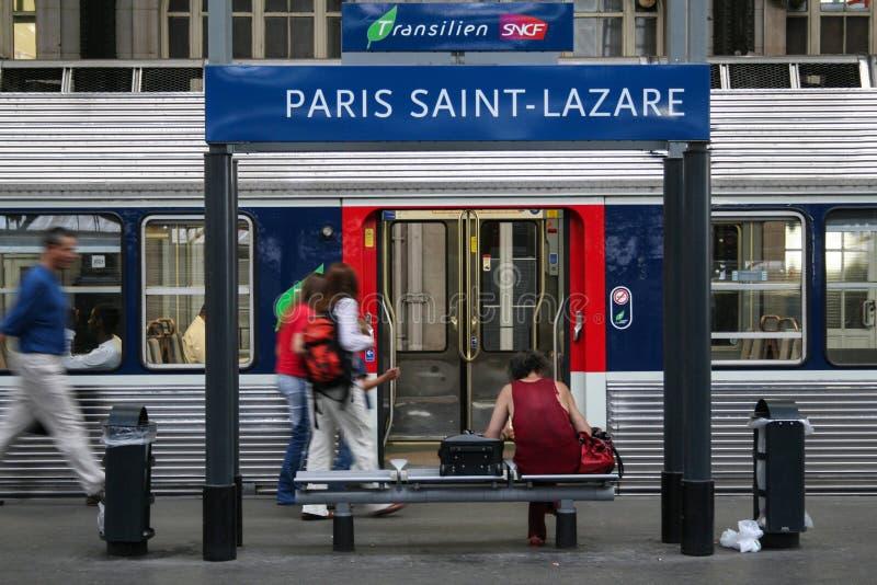 Pasajeros que acometen cerca de un tren suburbano en una plataforma de la estación de tren de Lazare del santo de Gare imágenes de archivo libres de regalías