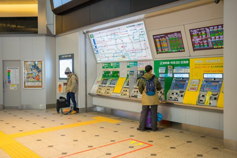 Pasajeros que compran el boleto de tren con la máquina del boleto en la estación de Tokio fotografía de archivo