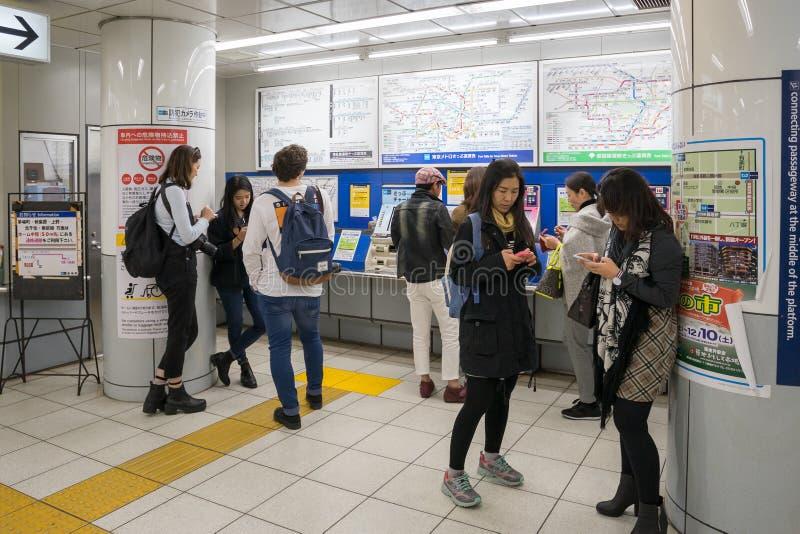 Pasajeros que compran el boleto de tren con la máquina del boleto en la estación de Tsukiji foto de archivo