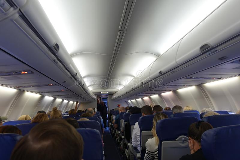 Pasajeros que esperan para sacar en un aeroplano fotos de archivo