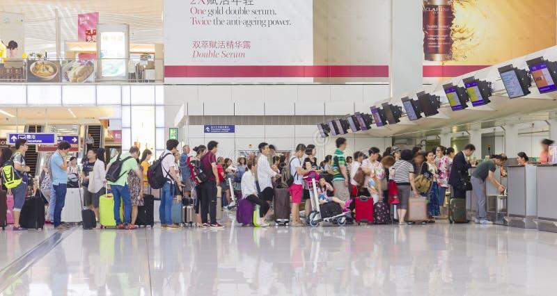 Pasajeros que hacen cola para arriba en contador de enregistramiento en Hong Kong International Airport fotos de archivo