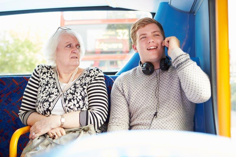 Pasajeros que perturban del hombre en viaje del autobús con llamada de teléfono fotografía de archivo