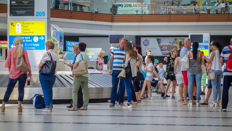 Pasajeros que se colocan en piso con equipaje en la estafa del equipaje del aeropuerto foto de archivo libre de regalías