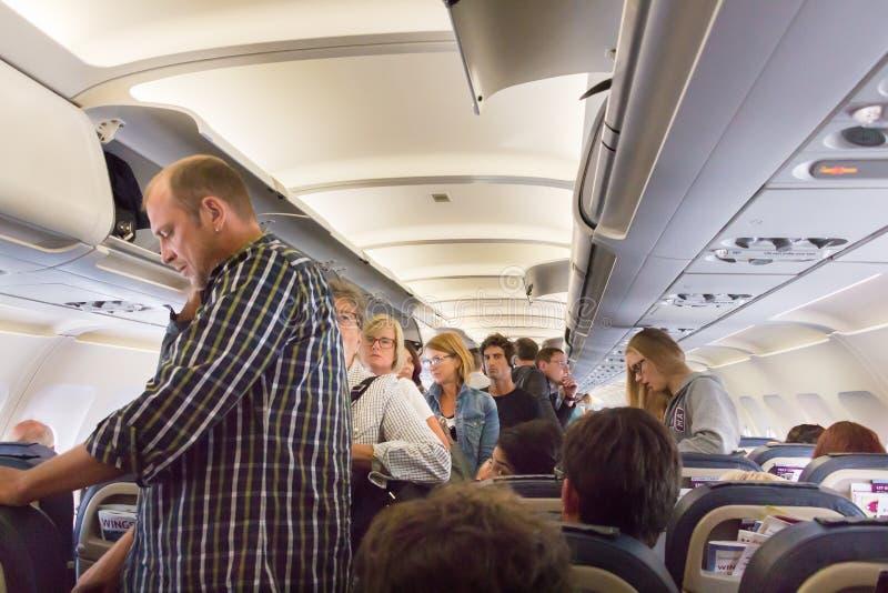 Pasajeros que se colocan para desembarcar de un aeroplano imagen de archivo libre de regalías