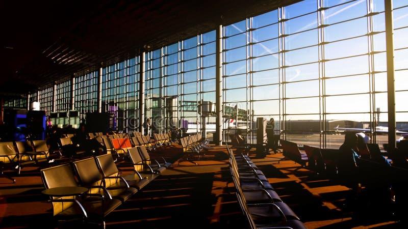 Pasajeros que se sientan en sillas en el terminal de aeropuerto, salón que espera iluminado por el sol espacioso fotografía de archivo libre de regalías
