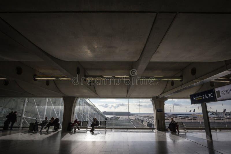 Pasajeros y viajeros que se sientan y que esperan delante de los aviones en el terminal 2 de CDG Roissy París Charles de Gaulle A foto de archivo