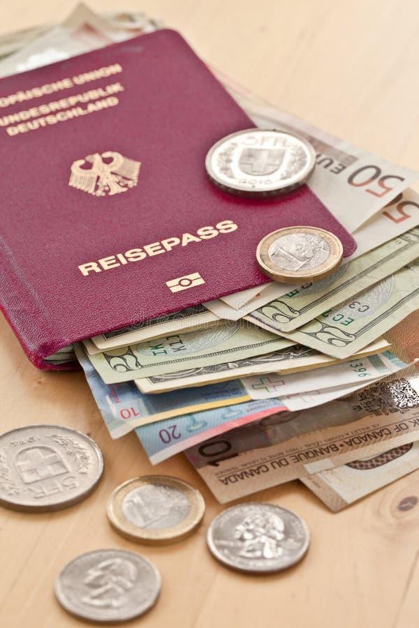 Pasaporte alemán y diversas monedas foto de archivo libre de regalías