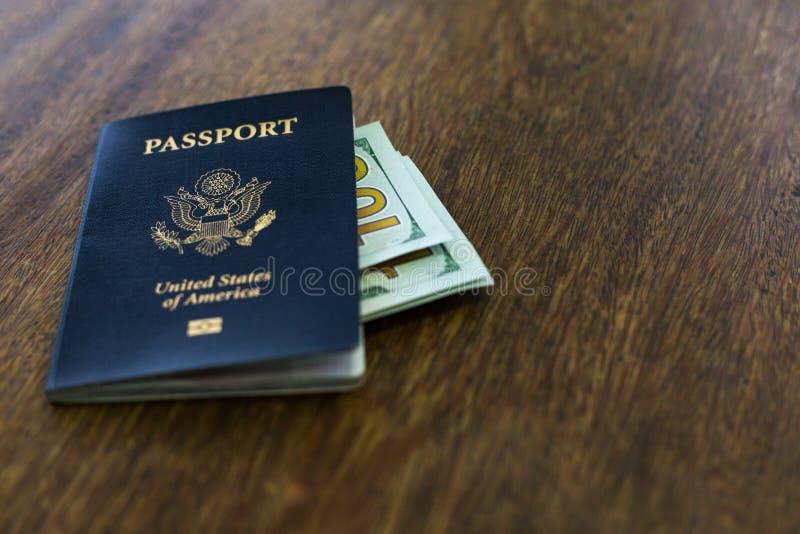 Pasaporte americano azul con algunos dólares de EE. UU. encima de un escritorio de madera foto de archivo