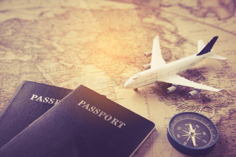 Pasaporte, avión, compás puesto en mapa - viaje del concepto imagenes de archivo