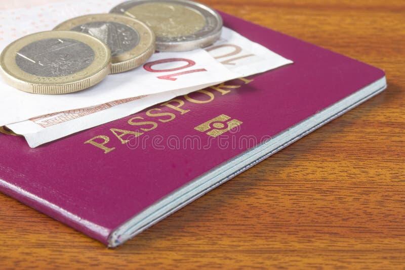 Pasaporte británico con las monedas y los billetes euro foto de archivo