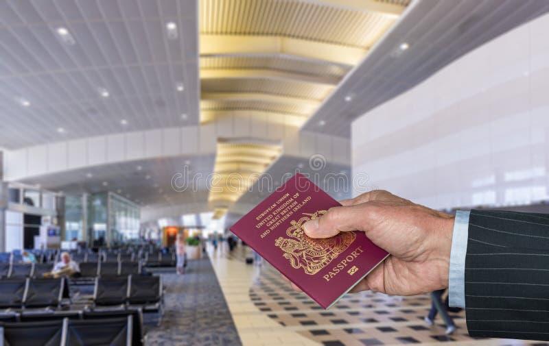 Pasaporte BRITÁNICO de la tenencia de brazo del ejecutivo 'senior' en el terminal de aeropuerto foto de archivo