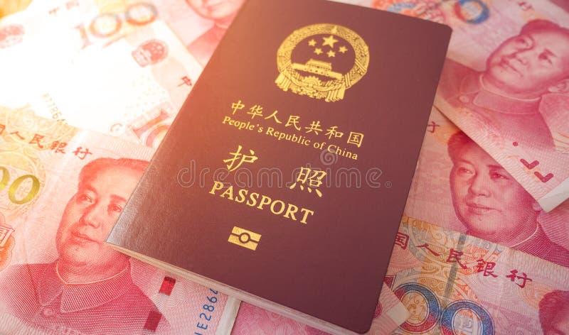 Pasaporte chino con unas notas de Yuan de 100 chinos fotos de archivo