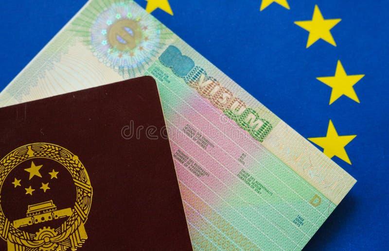 Pasaporte chino en bandera europea con la visa de Schengen foto de archivo