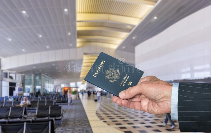 Pasaporte de los E.E.U.U. de la tenencia de brazo del ejecutivo 'senior' en el terminal de aeropuerto fotografía de archivo libre de regalías