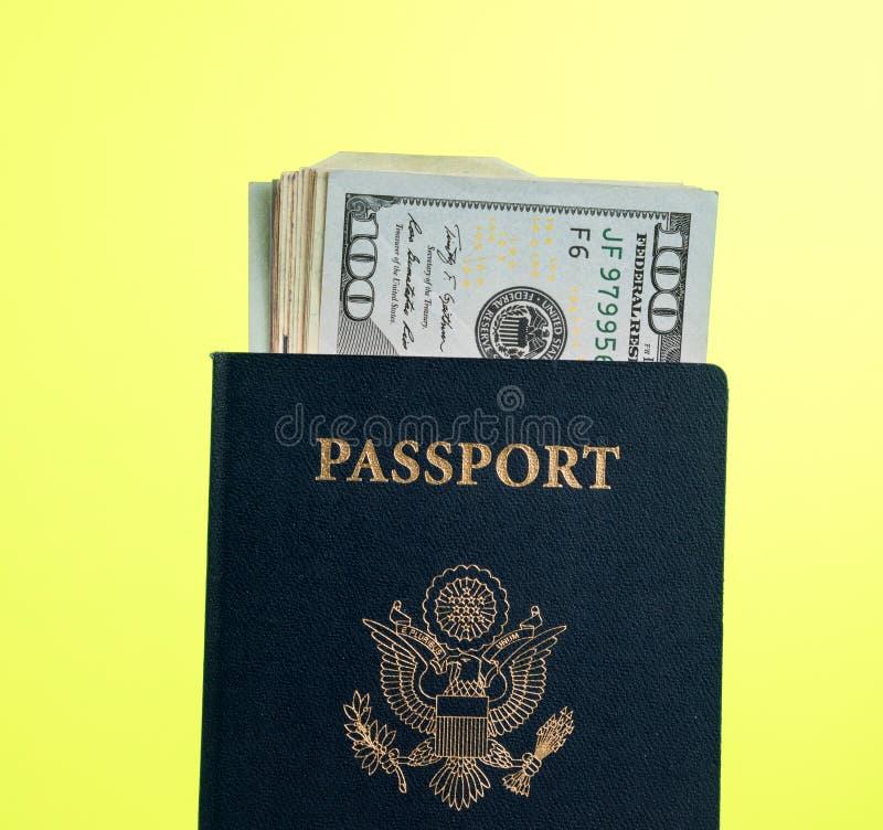 Pasaporte de los E.E.U.U. que sostiene una pila de billetes de dólar para el concepto del viaje fotografía de archivo