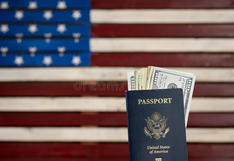 Pasaporte de los E.E.U.U. que sostiene una pila de billetes de dólar para el concepto del viaje foto de archivo