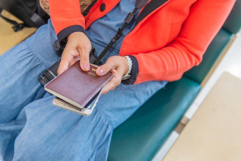Pasaporte del control de la mujer a disposición que espera su vuelo en el aeropuerto imagen de archivo