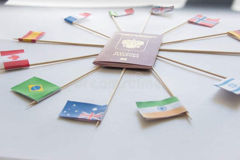 Pasaporte extranjero de la Federación Rusa y banderas de los países diferentes alrededor: La India, el Brasil, Reino Unido, Itali fotos de archivo libres de regalías