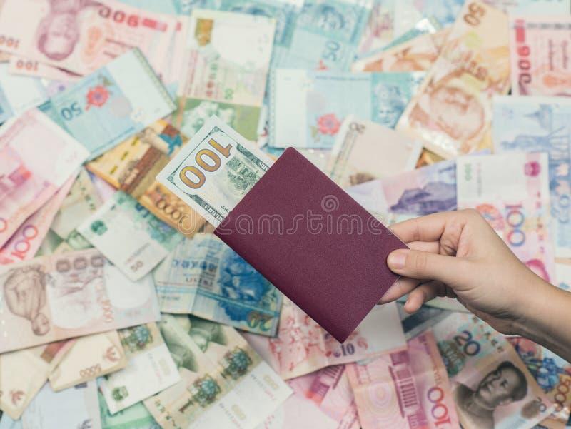 Pasaporte femenino del viaje de la tenencia de la mano con cientos dólares de EE. UU. dentro en el fondo de la textura del dinero imagenes de archivo