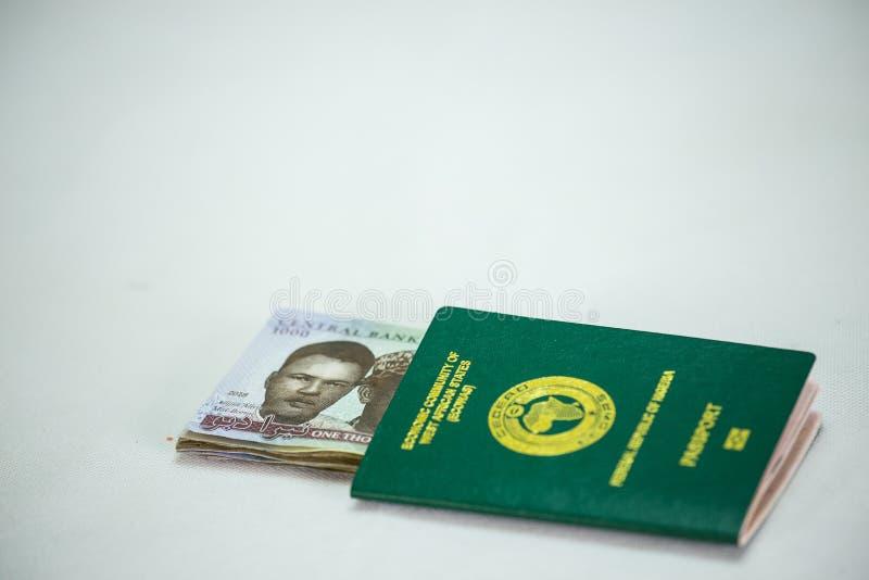 Pasaporte internacional de Ecowas Nigeria con 1000 notas de la moneda del naira imagen de archivo