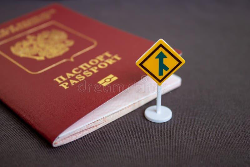 Pasaporte internacional ruso con una señal de tráfico amarilla de la flecha - concepto de la migración fotografía de archivo libre de regalías